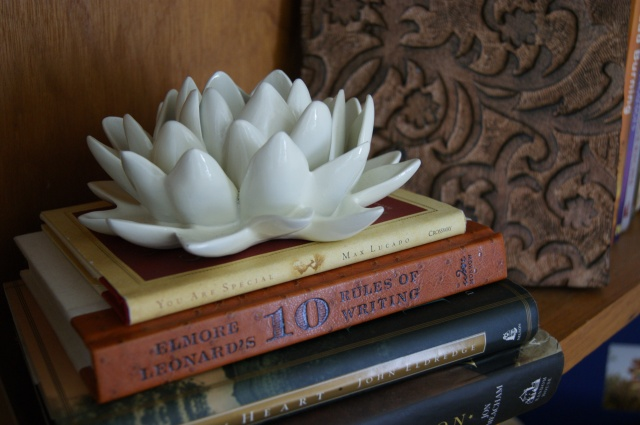 books on our bookshelf and a ceramic bloom